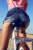 picture of short legs  - fashion outdoor photo of woman legs in jeans shorts sitting on bicycleriding by summer beach - JPG