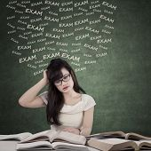 picture of dizziness  - Portrait of female student studying with textbooks to prepare exam and looks dizzy - JPG