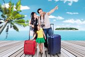 picture of carry-on luggage  - Portrait of happy family arriving at the pier of the resort island while carrying their suitcase - JPG