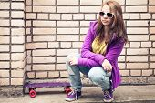 image of snickers  - Blond teenage girl in a sunglasses with skateboard sits near urban brick wall photo with retro tonal correction effect instagram old style filter - JPG