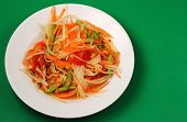 foto of green papaya salad  - thai hot papaya salad with a green background - JPG