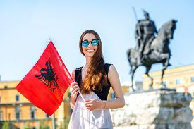 foto of albania  - Young Albanian patriot standing with flag in the center of Tirana city - JPG
