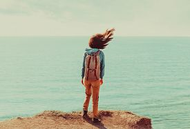 foto of flutter  - Traveler young woman with backpack standing on coastline near the sea in windy weather her hair fluttering in the wind - JPG