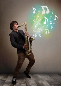 picture of saxophone player  - Attractive young musician playing on saxophone while musical notes exploding - JPG