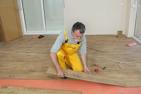 image of laminate  - Adult male worker installing laminate floor floating wood tile - JPG