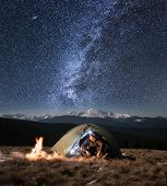 Male Tourist Have A Rest In His Camping In The Mountains At Night. Man With A Headlamp Sitting Near poster