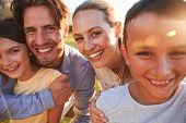 Portrait of happy white family embracing outdoors, close up poster