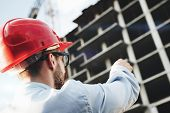 Architect Or Safety Officer In Red Hard Hat On Background Of Construction Site. Engineer Builder Man poster
