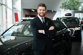 Smiling young male dealer in suit with arms folded standing in front of a new car at the dealership poster