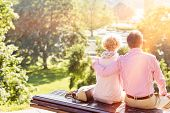Back view of middle-aged couple relaxing on park bench poster