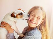 Happy child with dog. Portrait girl with pet. Jack Russell licks a teen poster