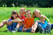 stock photo of happy kids  - A group of happy kids sitting in a meadow on a bright sunny day - JPG