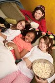 stock photo of foursome  - Little girls at a sleepover eat popcorn and tortilla chips - JPG