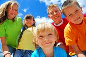image of children group  - A group of five happy kids with a blue sky behind them
