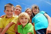 picture of happy kids  - A view looking upwards at five happy smiling kids with blue sky and wispy white clouds in the background - JPG