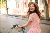 Smiling happy girl in dress and hat riding retro bicycle on a city street and looking at camera poster