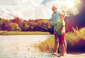 family, generation, summer holidays and people concept - happy grandfather and grandson with fishing poster