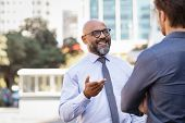 Smiling mature african businessman talking to his colleague outside the office. Two cheerful busines poster