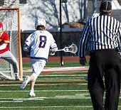 A High School Lacrosse Player Is Running Toward The Goalie Carrying The Ball In The Net Of His Stick poster