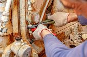 Dismantling Of Old Plumbing. Close Up Of Plumbing Hands With Adjustable Wrench poster