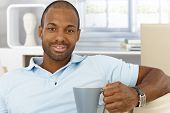 Portrait of cheerful handsome black man sitting at home with mug handheld, drinking tea, smiling at