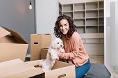 Moving To New Modern Apartment Of Joyful Young Woman Finding A Little White Dog In Carton Box. Smili poster