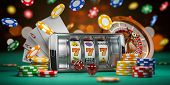 Online casino. Smartphone or mobile phone, slot machine, dice, cards and roulette on a green table i poster