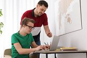 Father Helping His Teenager Son With Homework Indoors poster