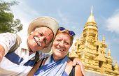 Senior Couple Taking Selfie At Golden Temple In Ko Samui - Happy Retired People Traveling To Thailan poster