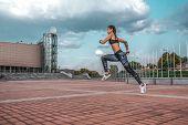 Muscular Girl Runs In The Summer In City, On A Morning Jog, High Jump. Sportswear Leggings Top. Phon poster