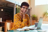 Happy brazilian girl with eyewear in coworking office with laptop looking at camera. Smiling african poster