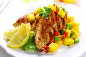 Grilled chicken breast with fresh mango salsa, soft focus