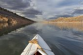 stock photo of horsetooth reservoir  - expedition decked canoe and wooden paddle on a narrow mountain lake  - JPG