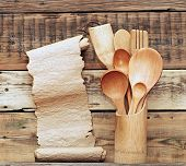 Kitchen wooden utensils in retro bucket with blank paper scroll over wooden background