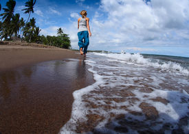 stock photo of wet pants  - Young lady walking on a wet sandy beach - JPG