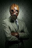 foto of gas mask  - Vintage businessman wearing a gas mask with retro wallpaper on background - JPG
