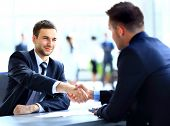 image of leader  - Two business colleagues shaking hands during meeting - JPG
