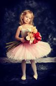 Pretty little girl ballerina in tutu posing over vintage background.