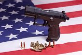 pic of ammo  - A conceptual image of a pistol and ammo on a US flag.