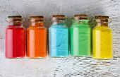 image of pigment  - Bottles with colorful dry pigments on wooden background - JPG