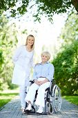image of take responsibility  - Pretty nurse taking care of senior patient while taking walk in park - JPG