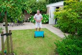 picture of potash  - Dutch retired senior fertilising his grass lawn as retirement activity with a blue fertilizer dispenser on wheels - JPG