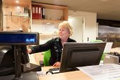 foto of cashiers  - Senior volunteer female cashier at work at the museum front desk - JPG