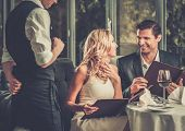 stock photo of cheers  - Cheerful couple with menu in a restaurant making order - JPG