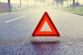 stock photo of breakdown  - Bad weather driving - warning triangle on a misty road ** Note: Shallow depth of field - JPG