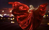 stock photo of blowing  - women dancing in silk dress artistic red blowing gown waving and flittering fabric night city street lights - JPG