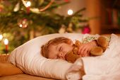 stock photo of dream home  - Little cute blond boy sleeping under Christmas tree and dreaming of Santa at home indoors - JPG