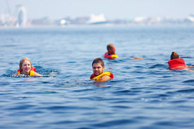 stock photo of pro-life  - people in life jackets swimming in open sea - JPG