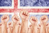 foto of labourer  - Iceland Labour movement workers union strike concept with male fists raised in the air fighting for their rights Icelandic national flag in out of focus background - JPG