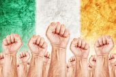 foto of labourer  - Ireland Labour movement workers union strike concept with male fists raised in the air fighting for their rights Irish national flag in out of focus background - JPG